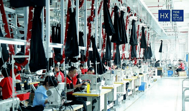 在狐轩服饰生产车间,机声隆隆,工人们正熟练地检查或操作各类机械设备,投入到正常生产图片