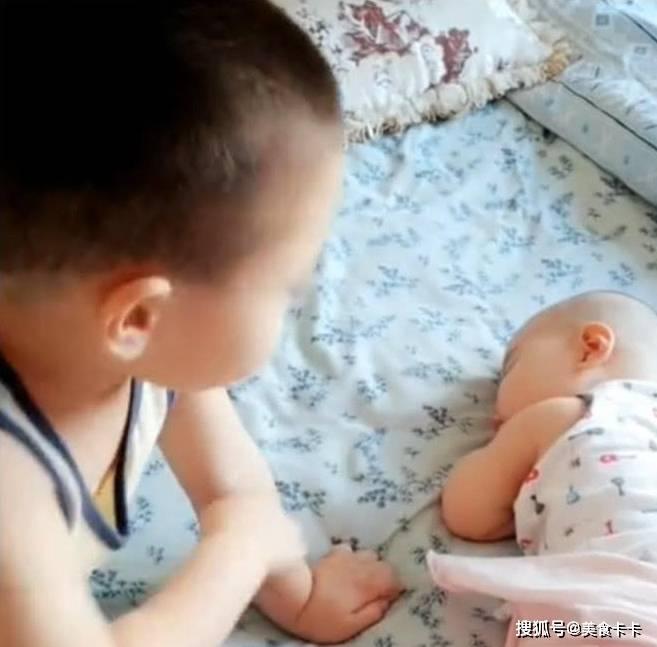 3岁的哥哥陪着妹妹在房间玩,妹妹睡着后,哥哥的动作很贴心