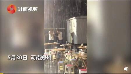 男子暴雨中顶纸板喝酒2小时